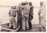 Fünf Mann, fünf Griffe. Gemeinsam lassen die THW'ler das Gewicht auf den Pfahl fallen und rammen ihn damit in den Boden. Quelle: THW /Neukölln